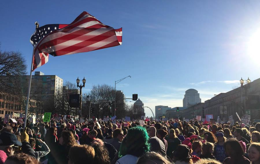 Protesters gather around an American flag, near the start of the march at Union Station. Nearly 20,000 people marched from Union Station to the Arch in support of women's rights.