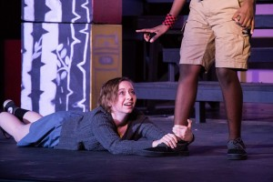 Helena, played by Sariah Henning, clings to Demetrius' leg, played by Charles Pearson. Demetrius rejects Helenia's affection for him.