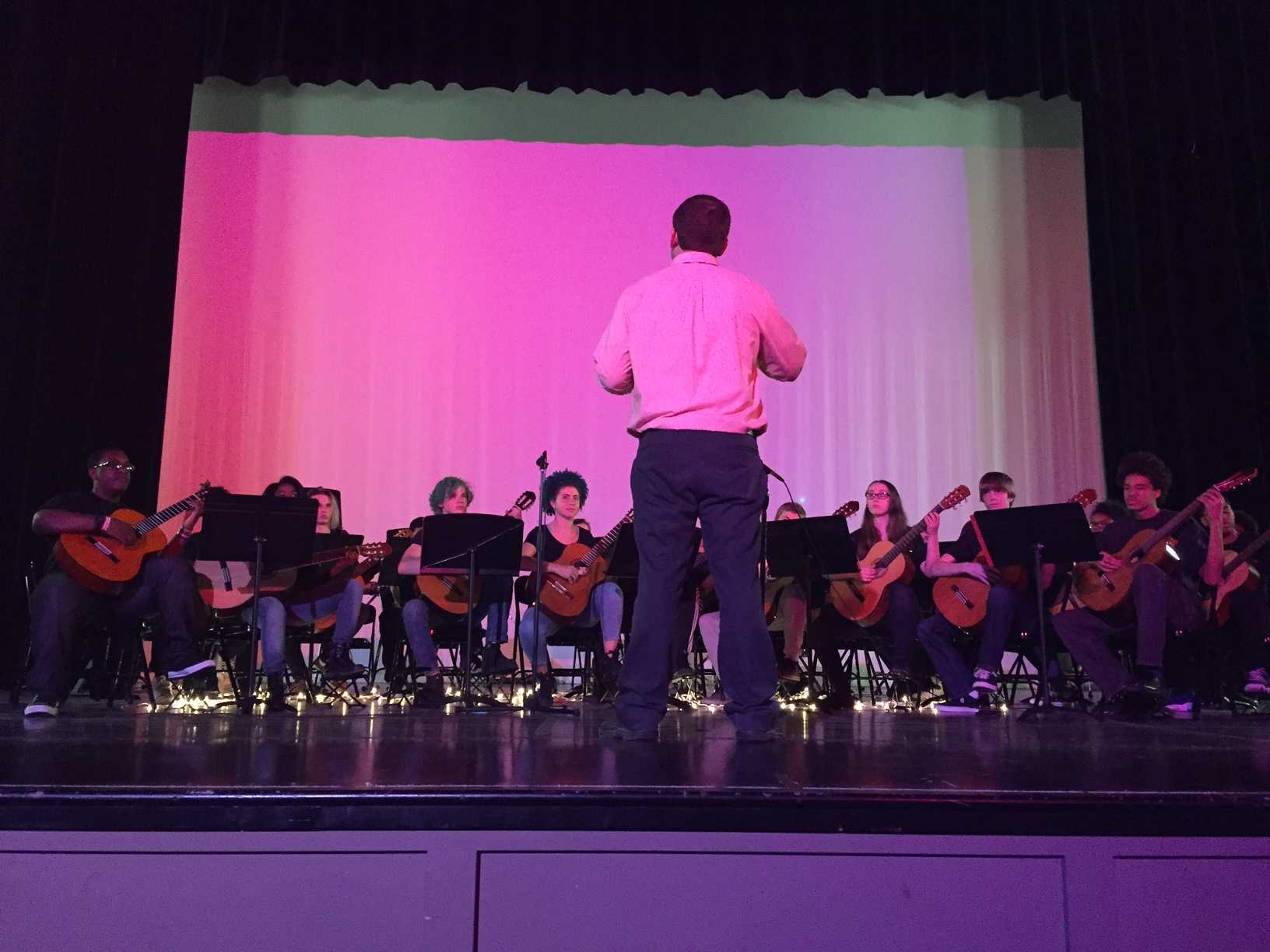 Dave Hagan, Guitar/Band, conducts high school guitar students. Hagan explained that each group of students performs a ten minute set. This also depends on what level students are at. Older students play longer pieces, while younger students play shorter pieces.