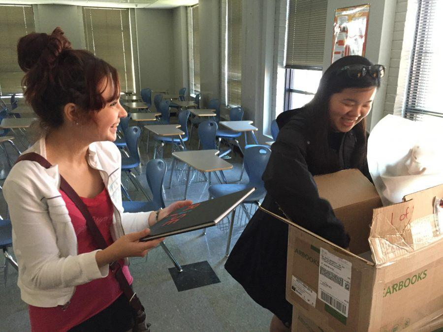 In a May 13, 2016 photo, Keeley Burke, 2017 Expression Editor-in-Chief (right) and Emma Iffrig, former Expression Editor-in-Chief (left), smile as they open the first box of newly delivered yearbooks. The 2016 Expression yearbook earned a first class rating from the National Scholastic Press Association.