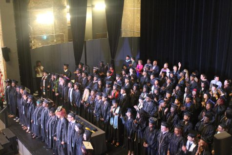 The class of 2017 stands on the stage, waiting for the National Anthem to be sung by choir students, standing in front.