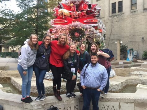 Caroline Knapp, Tessa Wild, Quinlan Holt, Elyse Luecke, Brooke Schuessler, Natalie O'Dell and adviser Travis Armknecht pose for a picture in downtown Dallas near Pegasus Plaza.