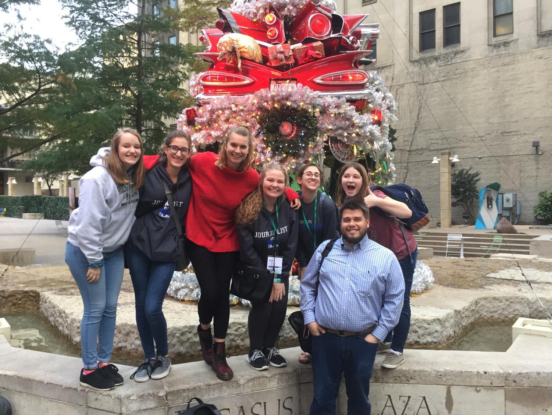 Caroline Knapp, Tessa Wild, Quinlan Holt, Elyse Luecke, Brooke Schuessler, Natalie O'Dell and adviser Travis Armknecht pose for a picture in downtown Dallas near Pegasus Plaza.
