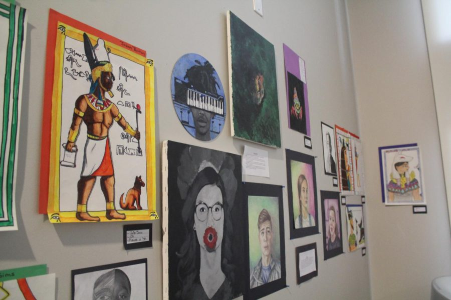 Various pieces of art hang on the wall in the mezzanine in the Sun Theater. The theme of this year's fall art show was