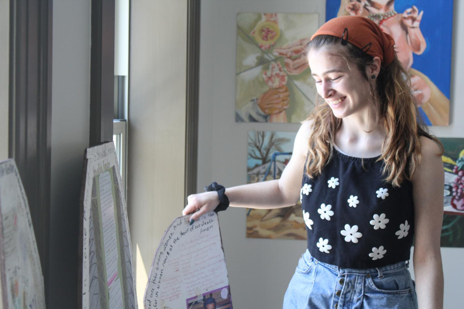 Kathleen Boesch, junior, sets up her display for her AP Art Studio portfolio project. In her project, she chose the explore how her upbringing in a Catholic school affected her upbringing. She does this by using Catholic imagery and stories into the paintings to symbolize her experiences.