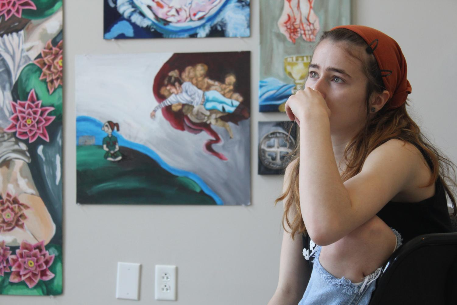 Kathleen Boesch, junior, takes a break from setting up her AP Art Studio Portfolio project. The pictures were intentionally arranged in a cross and put in symbolic order.