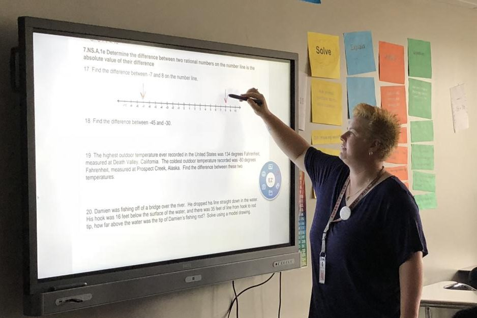 Middle school math teacher Elisabeth Reeder demonstrates determining the difference between two rational numbers using the BenQ interactive board in her classroom.
