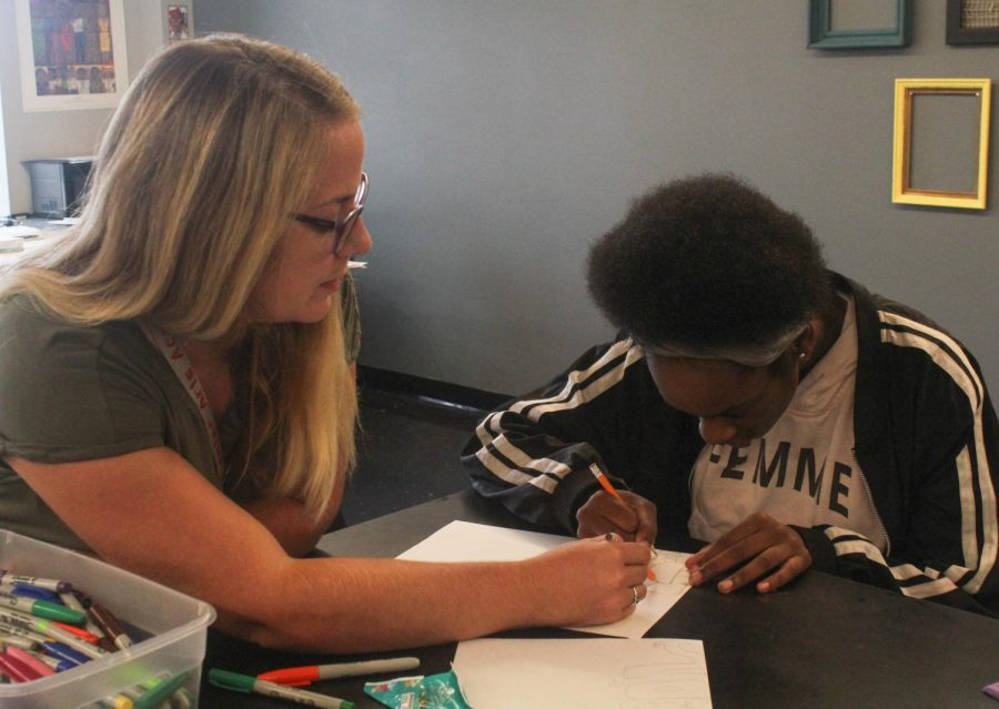Kelly Baker, visual arts teacher, instructing a advising a student on what to do.