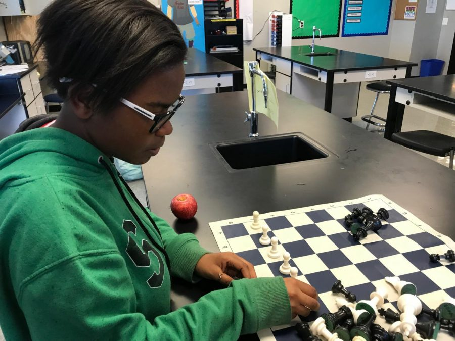 D'Ashia Miller sets up the pieces for a game of chess.