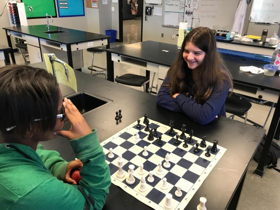 Molly Moen (right) laughs while playing chess with D'Ashia Miller (left).