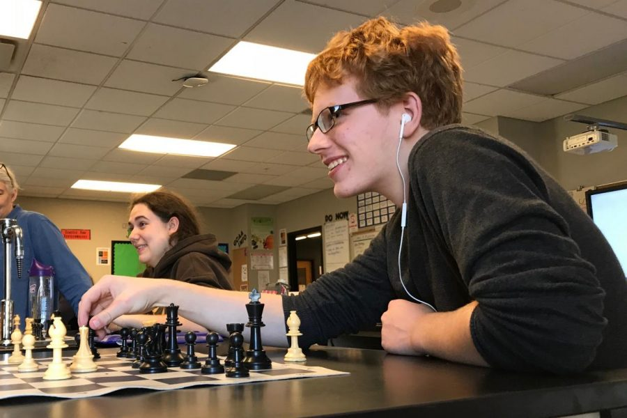Gabe Gibert talks and laughs as he plays chess and makes his next move.