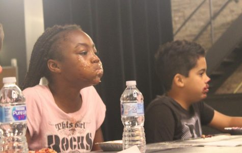 Sixth grader Nala Lindsey takes a breath after she wins the first round of GCAA's Pie Eating Contest.