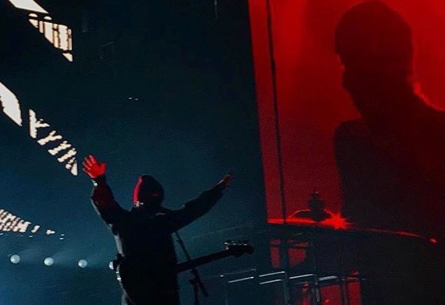 Tyler Joseph with his arms in the air as he greets the crowd.