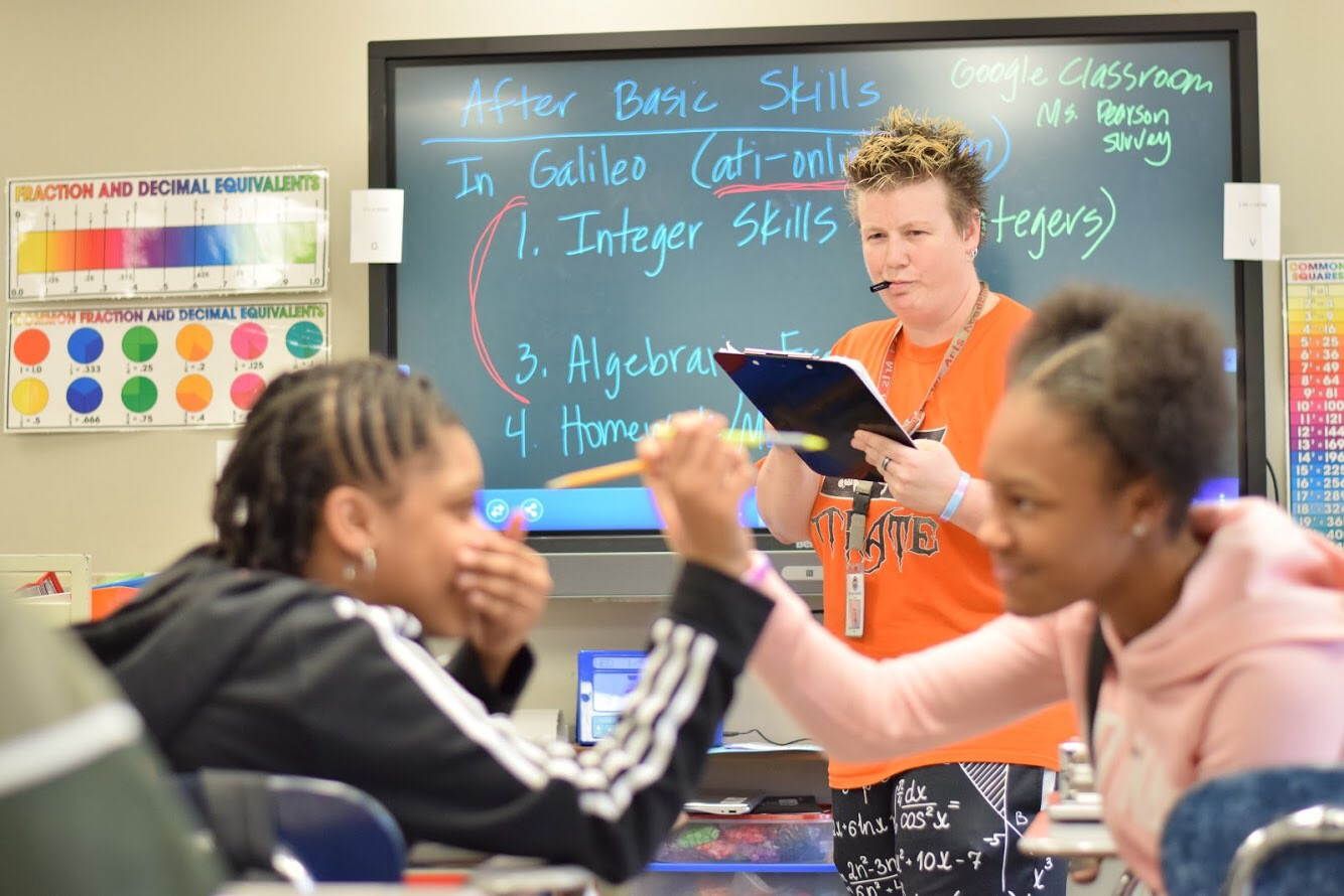 Photo illustration.  7th grader India Mitchell and 7th grader Janelle Briggs horseplay in math class as 7th Grade Math teacher writes them up for minors on her clipboard.