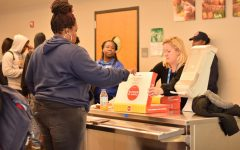 Guidance counselor Kim Campbell distributes donuts during an attendance incentive party.