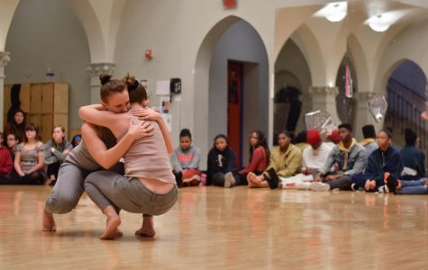 Students from both high school and middle school spectate as Iowa University students perform a piece representing reaching out and supporting a friend through their hardships to demonstrate how dance can be used to express emotion and to tell stories.
