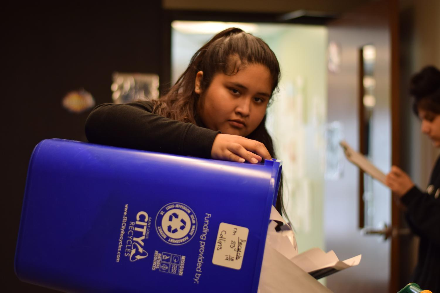 Seventh grader Aelilian Ceron'-Reyes dumps waste from a classroom recycling bin into the main recycling can.
