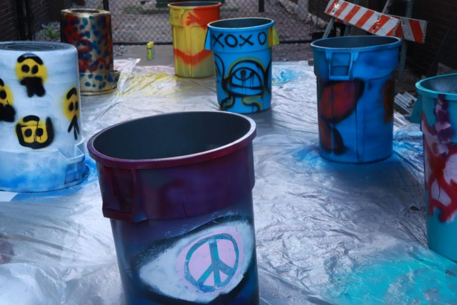 Students let their newly painted unfinished trash bins dry. Each bin with a unique design and/or pattern.