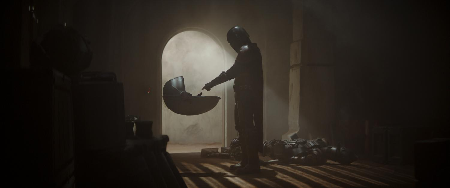 The Mandalorian reaches into the Infant's floating crib after fighting through his captors. Photo courtesy of Disney+